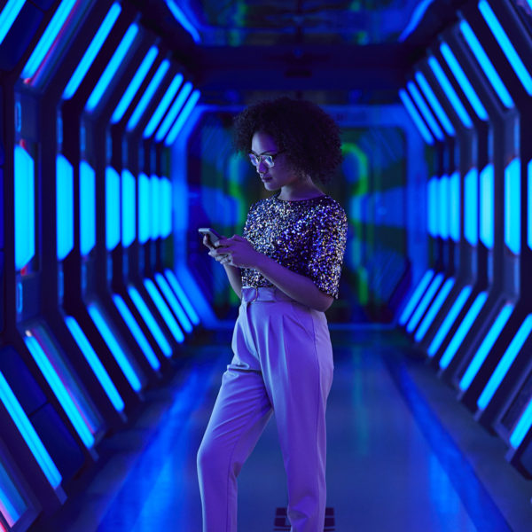 Young businesswoman looking at smartphone in spaceship-like corridor
