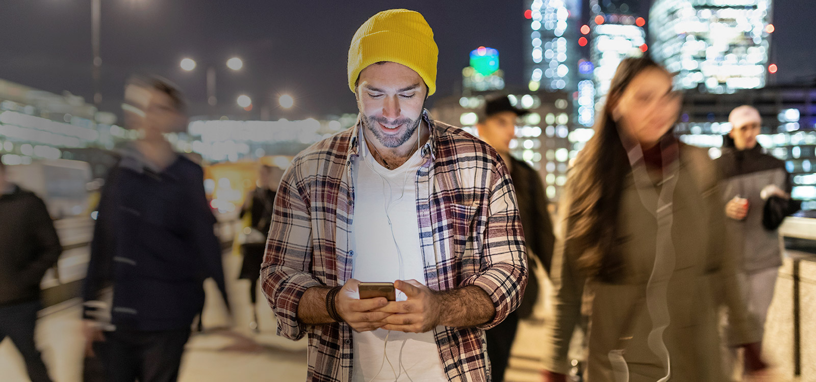 Smiling man looking at his phone by night with blurred people passing nearby